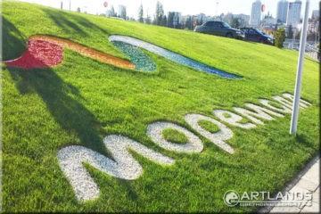 Декоративный цветной щебень для ландшафтного дизайна от мастерской ландшафта Art Lands купить и логотип на газоне